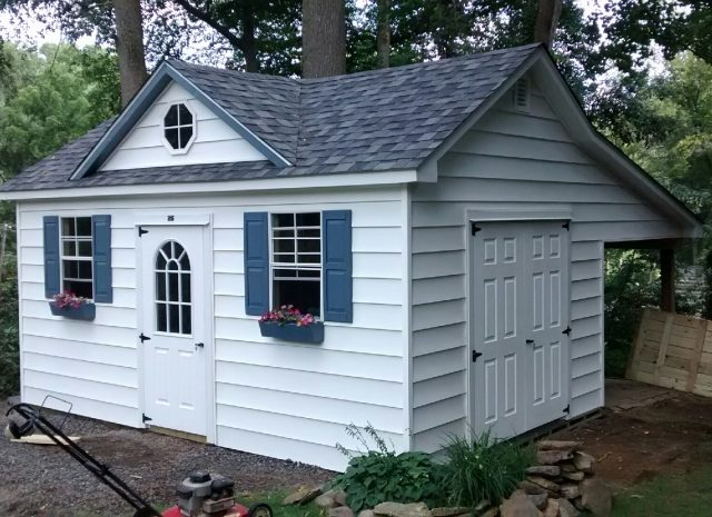 cape cod style dormer shed with white siding and blue shutters