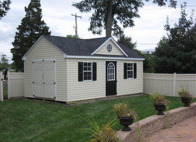 cream cape code dormer shed in a pa backyard