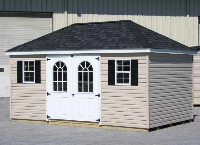 cream hip roof storage shed with doors that have windows