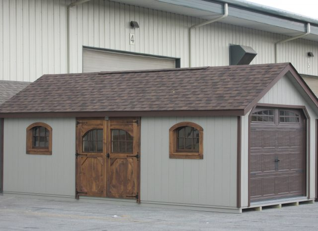 a frame garden style single car garage with wood doors