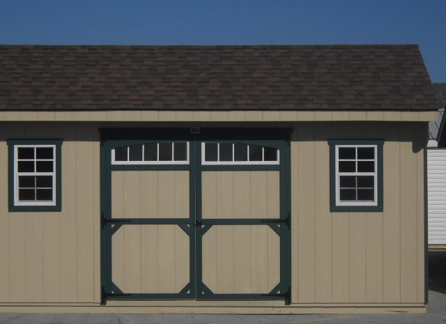 tan quaker style shed with green trim and windows in the doors