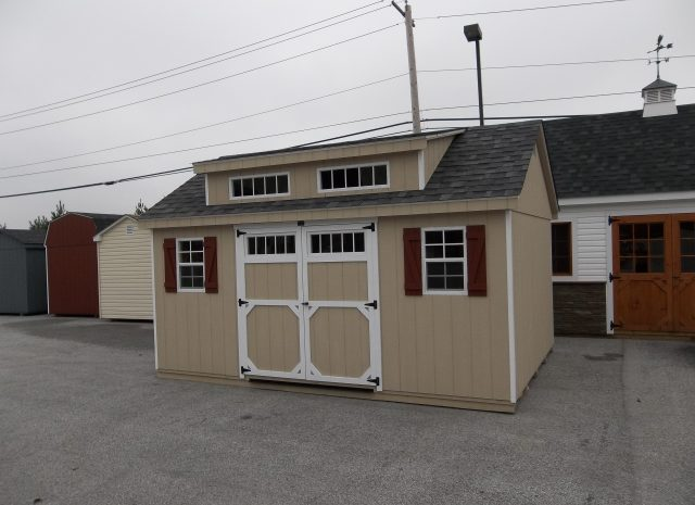 transom dormer shed with tan siding and red shutters